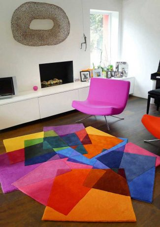 White Living Room with Pink Chair and Colorful Rugs