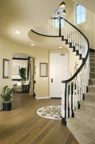Modern entry way with wood floor and winding stairs