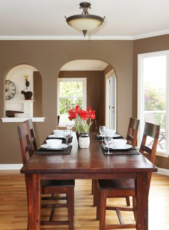 Nice place setting on wood dining room table with vase