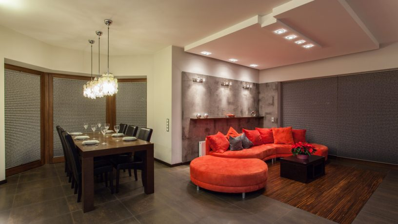 Unique dining room with red couch and solid table