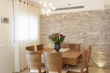 Wood dining room table with stone wall