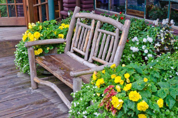 Wood backyard bench in flowers