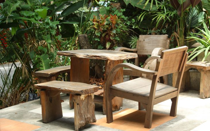 Wooden table and chairs in lush garden