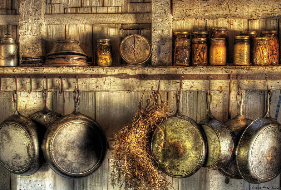 Spices and hanging frying pans in rustic kitchen